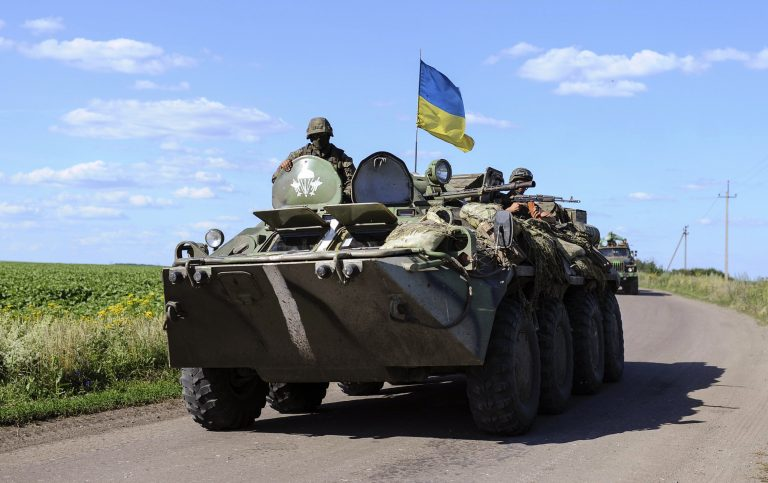 Ukrainian soldiers drive a military vehicle with a Ukrainian flag at a checkpoint near Slaviansk in eastern Ukraine July 3, 2014. About half the 130,000 residents of Slaviansk are thought to have fled since fighters who want eastern Ukraine incorporated into Russia took control of the city in April, a month after Moscow annexed the Black Sea peninsula of Crimea. Since then, government forces trying to end the rebellion in towns and cities across the Russian-speaking region have pounded separatist positions in and around Slaviansk. Picture taken July 3, 2014. REUTERS/Andrew Kravchenko/Pool (UKRAINE - Tags: POLITICS CIVIL UNREST MILITARY)